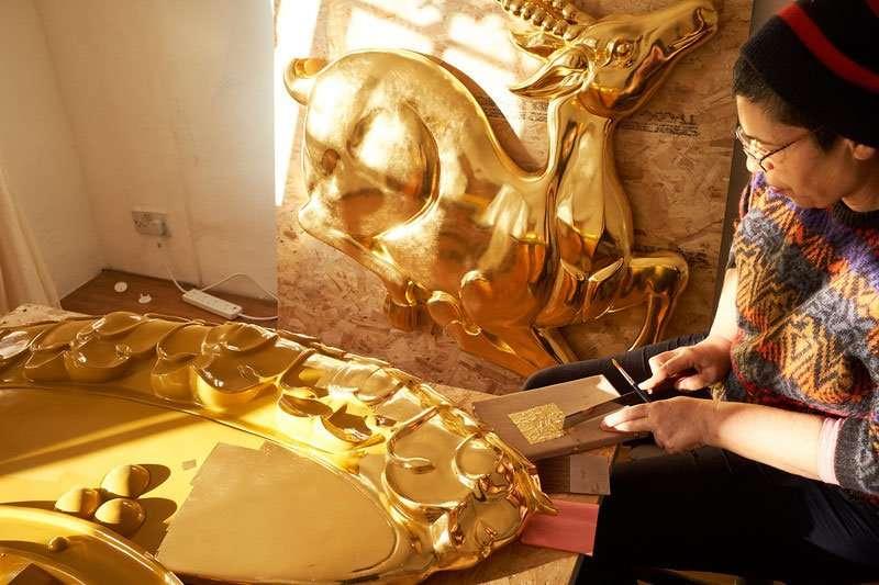 dharma wheel being gilded at Kadampa Art Studio